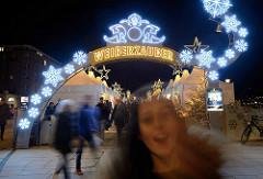 Weihnachtsmarkt am Jungfernstieg in der Innenstadt von Hamburg - beleuchtete Schneeflocke und Leuchtschrift Weißerzauber.