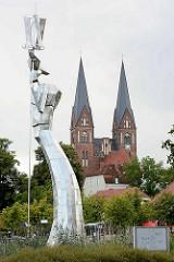 Moderne Edelstahlskulptur Parzival am See - Höhe 17 Meter, Künstler Matthias Zágon Hohl-Stein. Einweihung 1998 zur Verleihung des Namens Fontanestadt. Im Hintergrund die Klosterkirche Sankt Trinitatis.
