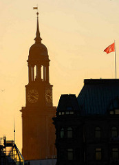 Sonnenuntergang in der Hansestadt Hamburg - Kirchturm der St. Michaeliskirche und Hamburg Flagge.