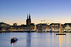 Weihnachtliches Hamburg - Blaue Stunde an der Binnenalster - beleuchtete Weihnachtsbäume; Blick zum Rathaus und Kaufhäusern am Jungfernstieg.