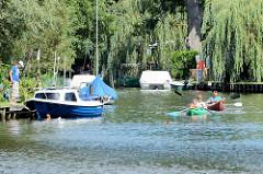 Bootsverkehr auf dem Rhin bei Alt Ruppin - Sportboote liegen am Steg, ein Kind badet.