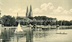 Ansicht vom alten Neuruppin - Blick vom Ruppiner See auf die Uferpromenade und Booten auf dem Wasser - Kirchtürme der St. Trinitatiskirche.