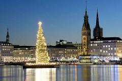 Beleuchtete Weihnachtstanne auf der Hamburger Binnenalster; dahinter die Türme der Katharinenkirche / Rathaus / St. Nikolaikirche.