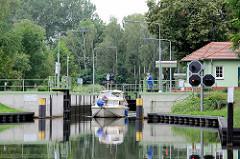 Tiergartenschleuse bei Oranienburg / Ruppiner Kanal; ein Sportboot verlässt die Schleusenkammer und fährt Richtung Oranienburg.