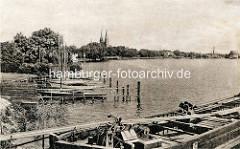 Alte Fotografie - Ufer mit Bootssteg und Booten am Ruppiner See. Kirchtürme der Klosterkirche St. Trinitatis von Neuruppin.