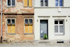Architekturfoto aus Neuruppin - architektonische Gegensätze, alt + neu. Verfallene Hausfassade mit abgebröckeltem Putz und freigelegtem Mauerwerk / Ziegelsteine neben glatter Putzfassade.