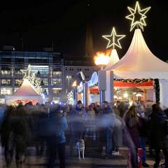 Weihnachtsmarkt am Hamburger Jungfernstieg - weisse Zelte mit Leuchtsternen; Marktbesucher.