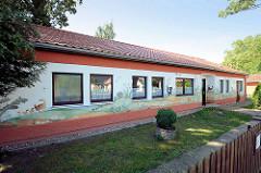 Haus der Generationen, ehem. Kindergarten in Karwe am Ruppiner See. Fassadenmalerei Künstlerin Dagmar Elsner-Schwintowsky.