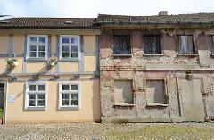 Wohnhäuser in Neuruppin - historische Architektur - Gegensätze, alt + neu. Restauriertes Fachwerkhaus mit blühenden Geranien an der Hausfront, daneben leerstehendes Wohngebäude mit abgebröckeltem Putz und freiliegenden Ziegelsteinen.