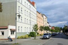 Mehrstöckige Wohnhäuser in der Bahnhofstraße in Neuruppin - im Vordergrund ein niedriges Flachdachgebäude, ehem. Laden.