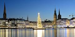 Blaue Stunde über Hamburg - Blick über die Binnenalster zur Hamburger Altstadt; Kirchtürme der St. Petrikirche, Katharinenkirche + Nikolaikirche; Turm vom Hamburger Rathaus - auf der Alster schwimmt die beleuchtete Weihnachtstanne.