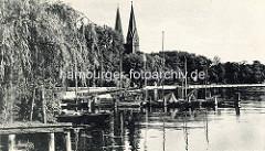 Historische Ansicht - Ufer mit Bootssteg und Segelbooten am Ruppiner See. Kirchtürme der Klosterkirche St. Trinitatis von Neuruppin.