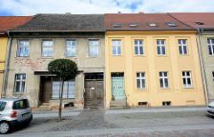Architekturfoto aus Neuruppin - architektonische Gegensätze, alt + neu. Verfallene Hausfassade mit abgebröckeltem Putz und freigelegtem Mauerwerk / Ziegelsteine neben glatter farblich abgesetzter Putzfassade.