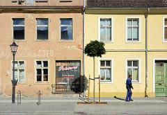 Wohnhäuser - Architektur Gegensätze Alt + Neu; leerstehendes Wohngebäude mit Geschäft, daneben Wohngebäude mit restaurierter Fassade; Architektur in Neuruppin.