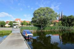 Städtischer Bootsanleger am Ruppiner See bei der Seepromenade von Neuruppin - re. die Kirchtürme der Kirche St. Trinitatis.