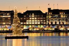 Schwimmende Weihnachtstanne auf der Hamburger Binnenalster, dahinter das Hotel Vier Jahreszeiten.