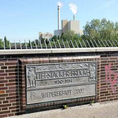 Schild an der Tiefstacker Brücke - Paar in Vierländer Tracht; im Hintergrund die Müllverbrennungsanlage an der Borsigstrasse in Hamburg Billbrook.