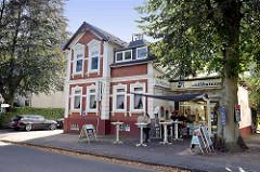 Gründerzeitgebäude mit Wohnungen - Anbau für Fischdelikatessen - Tische für Mittagstisch im Freien; Glißmannweg in Hamburg Schnelsen.