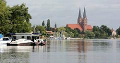 Ufer mit Bootssteg und Segelbooten am Ruppiner See. Kirchtürme der Klosterkirche St. Trinitatis von Neuruppin.