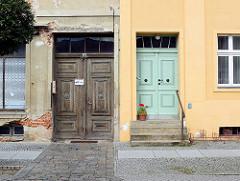Architektur alt + neu; Holztür mit Leisten und Schnitzerei, abbröckelnder Putz und Ziegelsteinen - farbige Putzfassade mit Holztür; Architekturfotografie in Neuruppin.