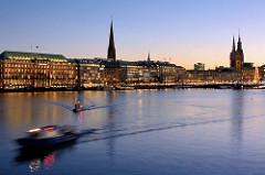 Abenddämmerung / Blaue Stunde an der Hamburger Binnenalster - Schiffe fahren zur Lombardsbrücke; Blick zum Ballindamm und dem Rathaus Hamburgs.