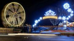 Weihnachtsmarkt Weißer Zauber am Jungfernstieg in der Hamburger Neustadt. Riesenrad in Bewegung - Schriftzug und winterliche Leuchtdekoration.