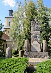 Kriegerdenkmal für die im 1. Weltkrieg gefallenen Dorfbewohner - im Hintergrund Dorfkirche