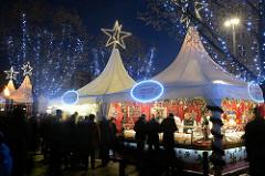 Weihnachtsmarkt am Hamburger Jungfernstieg - weisse Zelte mit Leuchtsternen; MarktbesucherInnen.
