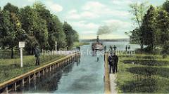 Colorierte historische Ansicht vom Dampfer Freya, der auf der Fahrt nach Neuruppin in die Schleuse einfährt. Der Schleusenwärter beobachtet die Einfahrt, das Schleusenpersonal offnet die Schleusenkammer von Hand.