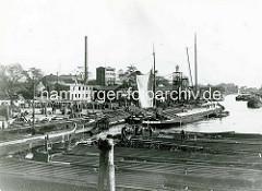 Hamburg Rothenburgsort früher: Schuten und Binnenschiffe liegen im Haken im Entenwerder Zollhafen - ein Ewer hat Segel gesetzt. Im Hintergrund Lagerfläche am Kai - Industriegebäude und der Wasserturm.