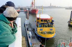 Ein Ausflugsschiff legt an der Alten Liebe in Cuxhafen an - im Hintergrund das Feuerschiff Elbe 1.