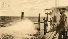 Seegang / hohe Wellen an der Alten Liebe in Cuxhaven - altes Bild, Männer mit Mützen stehen auf dem Holzsteg nahe der Gischt.