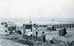 Historische Fotografie vom Badeort Duhnen an der Nordsee - Sandburgen mit Strandkörben; Badegäste, Frauen und Mädchen mit Kleidern und Hüten, Jungs mit Mützen.