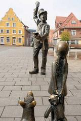 Skulptur der Utröper / Ausrufer, Bildhauer Frijo Müller-Belecke am Kirchplatz in Otterndorf - im Hintergrund das gelbe Barockgiebelhaus, eines der ältesten Wohnhäuser der Stadt - erbaut 1731,
