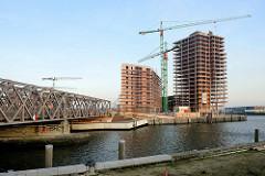 Blick über den Magdeburger Hafen in der Hamburger Hafencity; lks. die Baakenbrücke - re. der Baakenhafen mit Baustellen am Versmannkai.