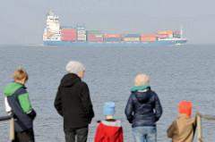 Containerschiff / Frachter auf der Elbe - Touristen am Ufer bei Otterndorf.