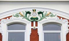 Jugendstildekor - Büste mit floralen Stuckelementen; Hausfassade in Cuxhaven.