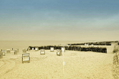 Strand mit leeren, verschlossenen Strandkörben - Nordseestrand in Duhnen / Cuxhaven - in Sand gesteckte Reisigbesen als Windschutz.