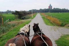Pferde ziehen einen Wattwagen über Neuwerk - im Hintergrund der alte Leuchtturm.