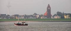 Fischkutter in Fahrt vor Cuxhaven. Im Hintergrund die Strandpromenade mit Garnisonskirche St. Petri.