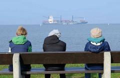 Elbufer - Blick auf die Elbe bei Otterndorf; Touristen sitzen auf einer Bank und blicken auf den Fluß - ein Containerschiff fährt in die Elbe ein.