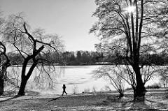 Winter in der Hansestadt Hamburg; Joggerin am zugefrorenen Stadtparksee - Gegenlichtaufnahme, die Sonne strahlt durch die kahlen Bäume.