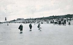 Historische Badeszene an der Kugelbake von Cuxhaven. Badegäste, Männer - Frau - Kind stehen mit hochgekrempelten Hosen, hochgerafftem Kleid.