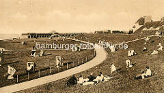 Historische Ansicht von Cuxhaven - Urlaubsgäste / Urlauber liegen im Gras am Deich, Strandkörbe auf der Wiese.