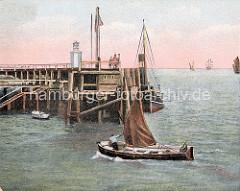 Einfahrt eines kleinen Segelschiffs in den Hafen von Cuxhaven - Holzsteg und Festfeuer / Signalfeuer an der Hafeneinfahrt.
