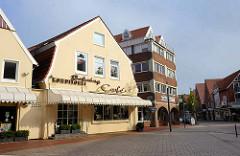 Wohn- und Geschäftshäuser unterschiedlicher Bauformen am Kirchplatz in Otterndorf.