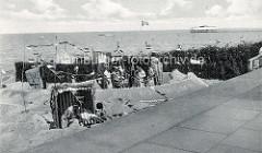 Historische Ansicht vom Strandleben in Duhnen - große Sandburg mit Muschelaufschrift Burg Kränzchen unter uns; Gruppe mit Frauen in Bademänteln - verschiedene Flaggen.