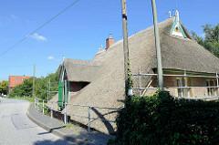 Kurfürstendeich in Hamburg Curslack - Reetdachhaus versteckt hinter dem hohen Deich.
