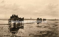 Altes Bild von Wattwagen auf dem Weg durch das Watt Richtung Insel Neuwerk - im Hintergrund die Insel mit Leuchtturm.