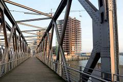 Die Baakenbrücke überquert den Magdeburger Hafen in der Hamburger Hafencity - im Hintergrund der Baakenhafen und Baustellen am Versmannkai.